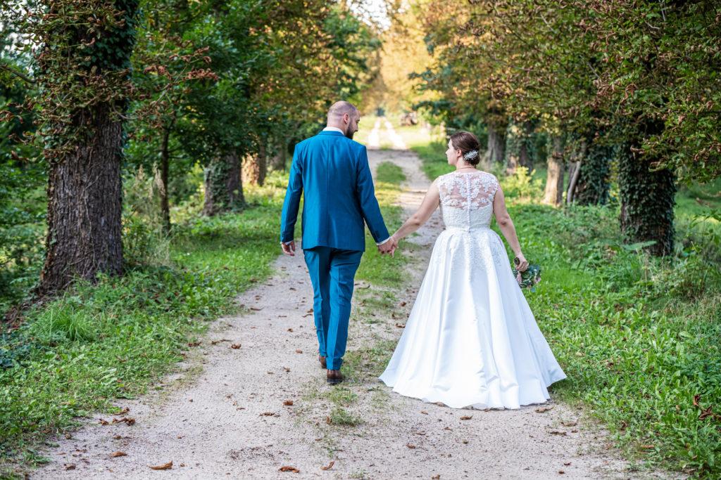 Brautpaar geht Baumallee entlang Ansicht von hinten